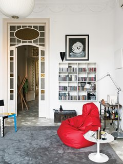 Vila D'Acosta-Calheiros hung a space-saving wall shelf in the library. The table is by Eero Saarinen; the Tolomeo lamp is by Michele de Lucchi for Artemide. The red beanbag-like Sacco chair is by Zanotta, as is the Sciangai coatrack in the hall, beyond.