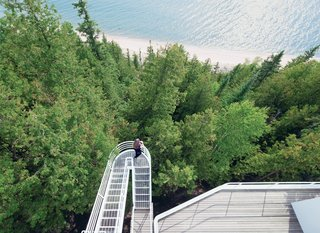 This Lake House Is a Living Piece of Architecture History - Photo 5 of 21 - Located on the shore of Lake Michigan, the 1973 Douglas House was one of architect Richard Meier's first residential commissions. Defined by its verticality, the house features an exterior stepped walkway that extends over the trees, connecting the levels.