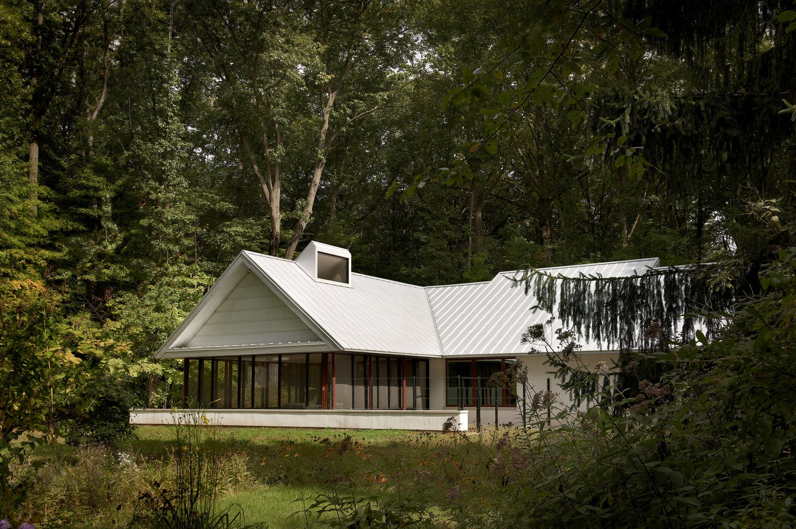 """Exterior, Farmhouse Building Type, House Building Type, Gable RoofLine, and Metal Roof Material """"When you're doing a second home, a lot of the character of the design is defined by what it isn't,"""" says architect Greg Howe, as a way of explaining the minimalistic approach that was taken on this Michigan weekend home. """"If you think of it as cold, you have to remember, the setting, and accessing nature, is the point.""""  Photo 1 of 8 in Modern Cottage Renovation in Michigan"""