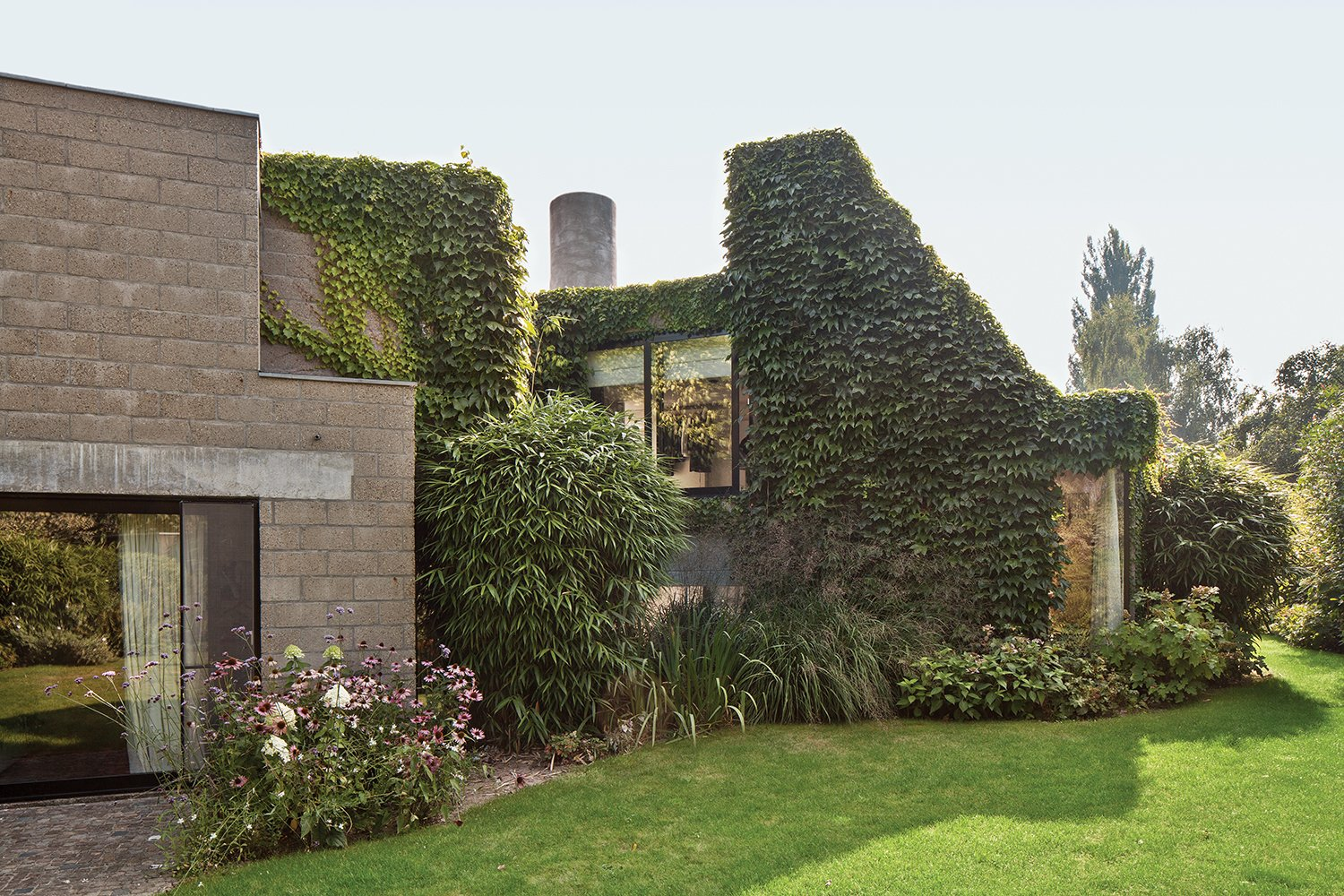 """Outdoor, Back Yard, Trees, and Grass """"This house is actually quite demanding; you have to be committed.""""—Resident Nathalie Vandemoortele  Photo 3 of 9 in A Concrete Home in Rural Belgium"""