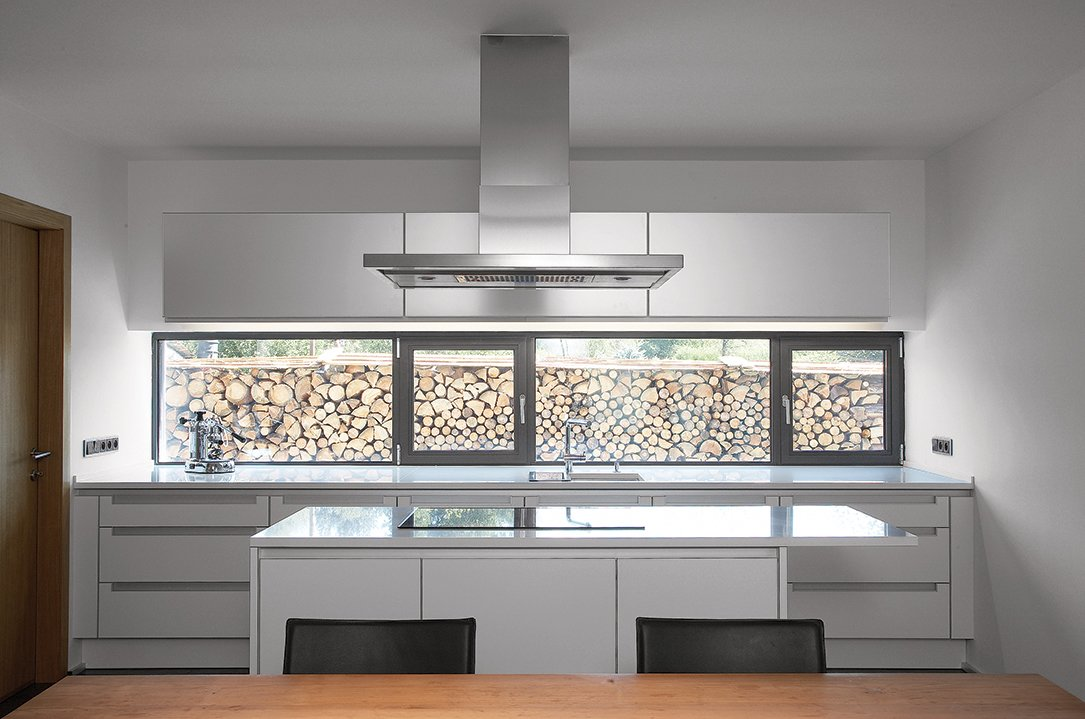 Kitchen and Range Hood In the kitchen, symmetrical, glossy surfaces keep the eating area clean.  Photo 4 of 4 in A Striking Bohemian Geothermal Home
