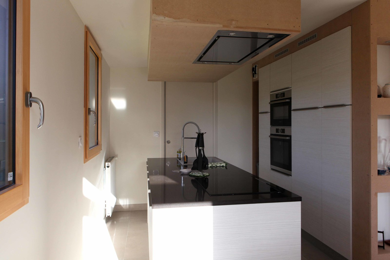 A low-pitched roof frames the third section of the home, which houses the kitchen and laundry room. Keeping the spaces small and separate allows for better insulation and temperature consistency throughout.  Photo 5 of 7 in A Cozy, Well-Sealed Cottage in Northwest France Goes Green