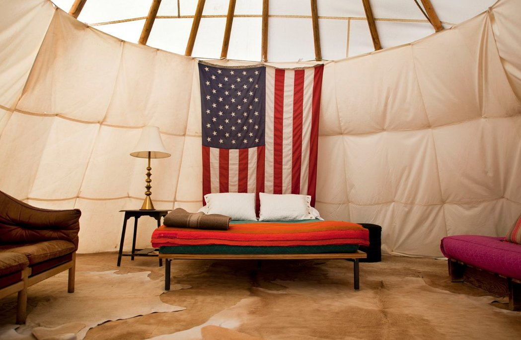 Bedroom, Lamps, Night Stands, Rug Floor, and Bed This interior shot of one of El Cosmico's teepees pairs life on the road with the American dream.  Photo 3 of 9 in Hotels We Love: El Cosmico Hotel in Marfa, Texas