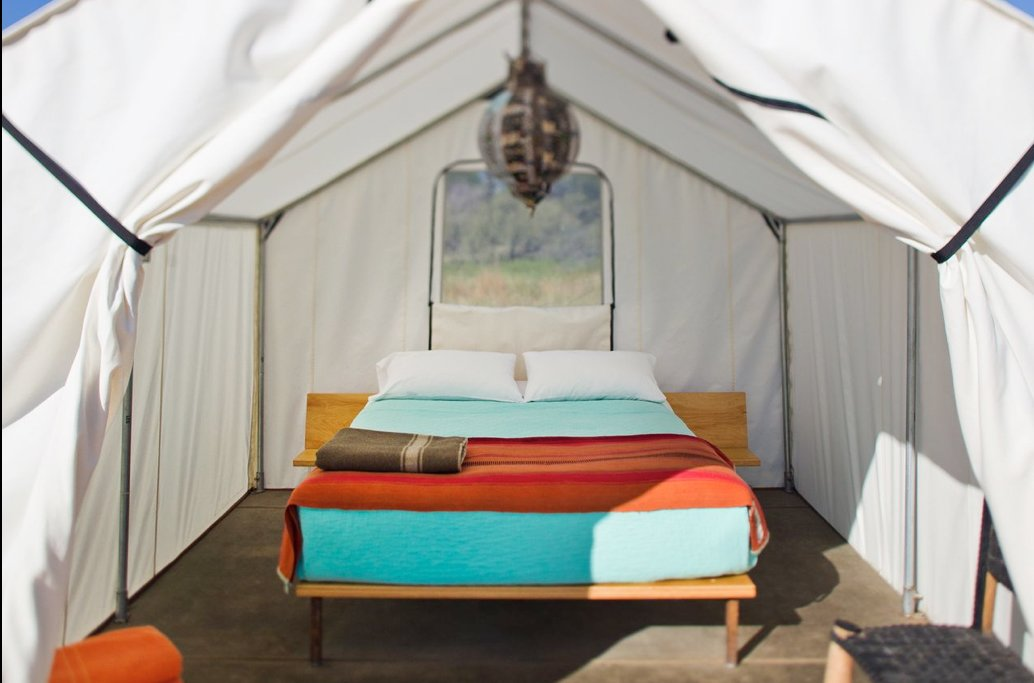 Brightly colored sheets and a central pendant lamp show this tent to its best advantage. Tagged: Exterior and Tent Building Type.  Photo 6 of 9 in Hotels We Love: El Cosmico Hotel in Marfa, Texas