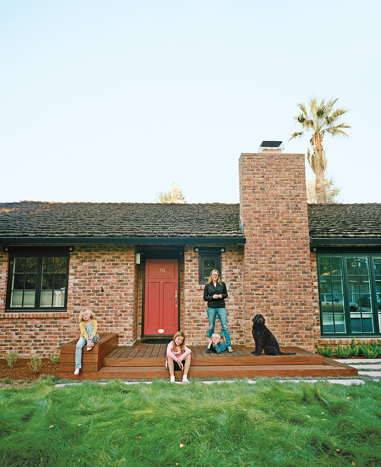 "Persin and her children, Lu, Mae, and Calvin, pose on their front stoop, built with ipe left over after the completion of the back deck. ""It looks lush—almost like a fur blanket,"" Persin says.  Photo 3 of 6 in Bay Area Ipe-Clad Backyard Getaway"