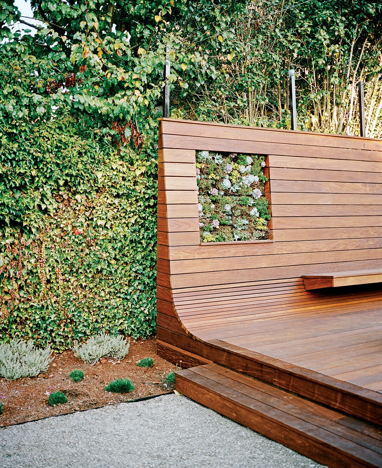 "Outdoor, Wood Patio, Porch, Deck, Small Patio, Porch, Deck, and Back Yard Cox initially conceived the deck as a conventional surface for relaxing and entertaining. With the bench, however, he seized an opportunity to create something both functional and visually arresting. ""You go down these paths and, as the design mutates, other ideas attach themselves and make it stronger and more interesting,"" he says.  Photo 4 of 6 in Bay Area Ipe-Clad Backyard Getaway"