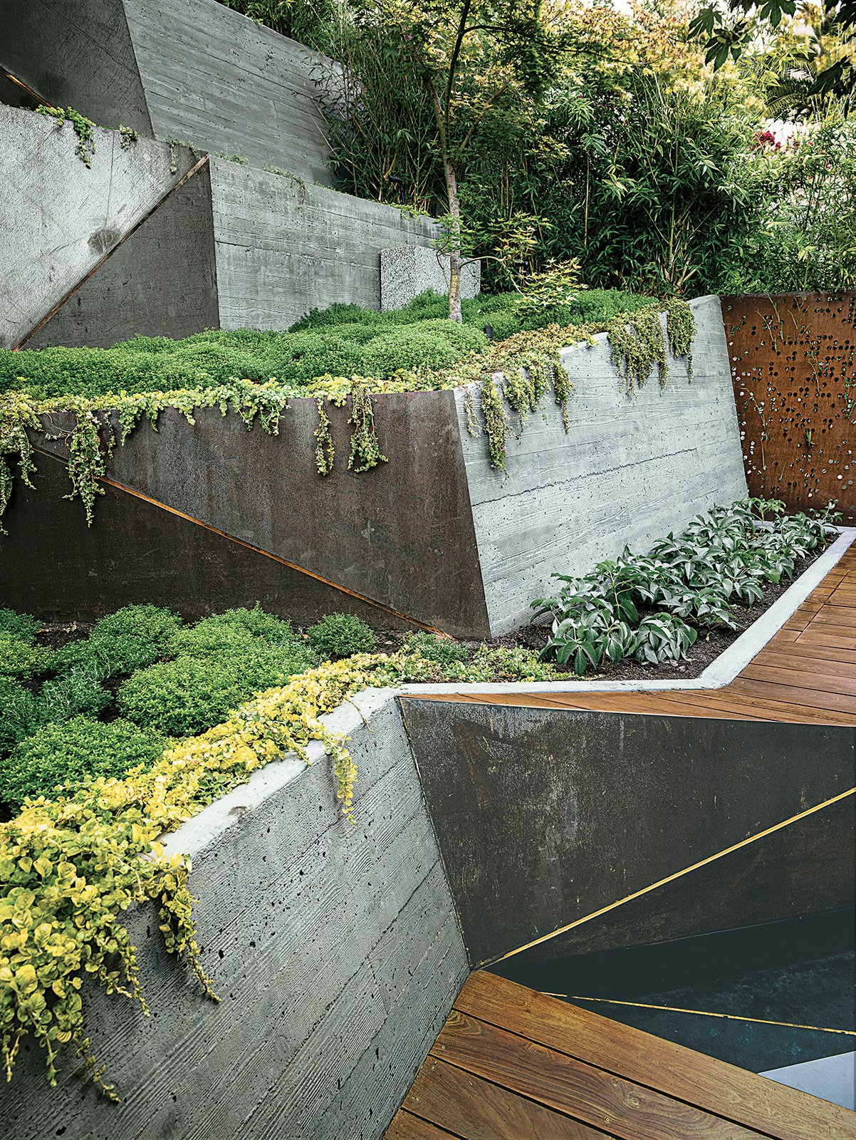 Outdoor, Raised Planters, Gardens, Small Patio, Porch, Deck, and Wood Patio, Porch, Deck Board-formed concrete retaining walls double as ramps from the deck to the garden's highest point.  Photo 4 of 4 in An Architect Sculpts Out a Tadao Ando-Inspired Backyard