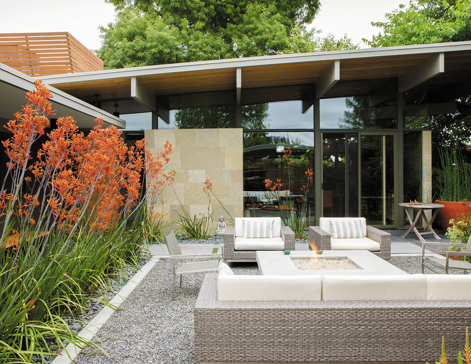 Exterior, Mid-Century Building Type, and Shed RoofLine Behind the resin screen is the property's centerpiece: an entry garden that Trainor recast as an outdoor living room. Sparta stacking chairs, a deep-wicker Baia sofa, and matching Baia armchairs, all by Mamagreen, are arranged around a custom concrete fire pit. Orange kangaroo paws lean in from the sides, creating a sense of privacy without sacrificing views. It's a welcoming space that serves as a casual gathering spot when the weather cooperates.  Photo 9 of 9 in Creative Landscape Design for a Renovated Eichler in California