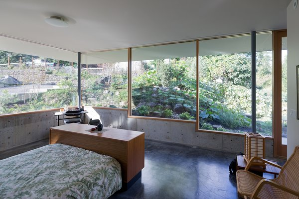 In the master bedroom, stepped windows framed by Douglas fir mullions rest on low concrete walls that are flush with the easy-to-maintain, hand-troweled concrete floor. The platform bed is from Scan Design and the rattan chair is from Ikea.  Photo 4 of 9 in This House Gets Better with Age