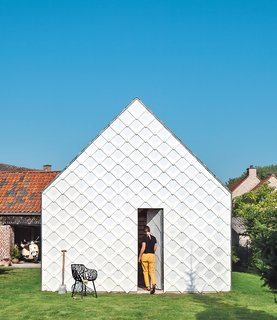 Architect Indra Janda hand-cut sheets of polycarbonate into 15¾-inch square shingles and clad the entire timber structure—a gabled roof and walls—with them.