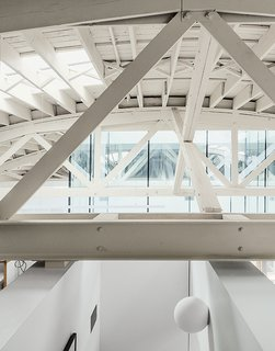 Architects William Neburka and Carrie Strickland set off some spaces with walls that stop shy of the bowstring trusses to preserve an overall sense of openness.