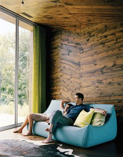 Stained-wood paneling, cut into chevrons for visual effect, create a warm, tactile interior of this house in Hennepin, Illinois.The irregular pattern of the paneling was inspired by the outlying prairie landscape and forest beyond. The green of the curtains and pillows brings out the verdant tones in the stained wood, and sparse furnishings keep the rooms from feeling overwhelming.