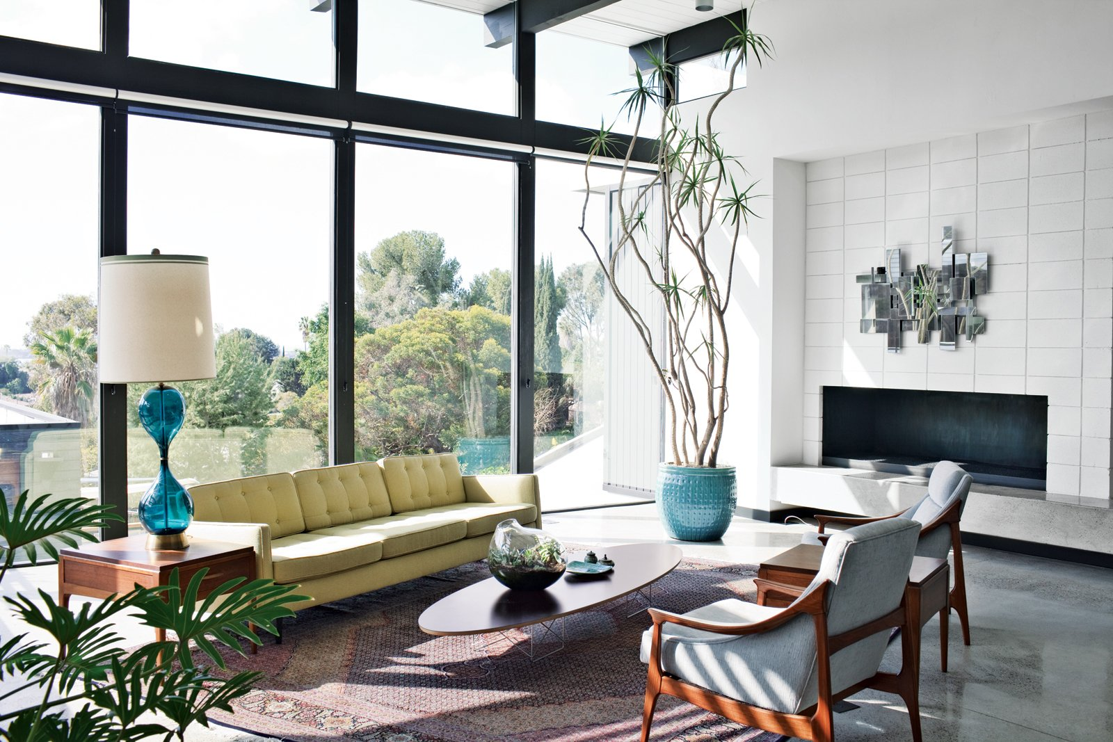 Modern home with Living Room, Concrete Floor, Sofa, Chair, Coffee Tables, Rug Floor, Table Lighting, End Tables, and Standard Layout Fireplace. A Nelson sofa sits on a handmade Persian Mahi rug in the living room. Photo  of Design Guide: San Diego