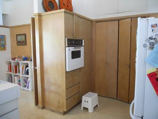 BEFORE: Prior to renovation, low-contrast wood cabinets obstructed the passage between the kitchen and the family room, giving both rooms a feeling of dullness in spite of the light tone of the wood and the walls around it.