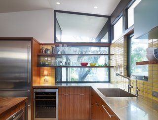 Opening the kitchen to outdoor spaces, a new window with floating shelves for storage looks out into the front yard.  New appliances, stainless steel countertops and an integral sink add utility. Photo by Whit Preston.