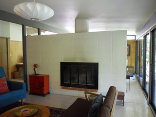 BEFORE: Looking disjointed, the living room in the pre-renovation Houser home is an alienated space, occluded from the natural light entering the spaces just beyond.