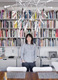 A second bedroom was converted into a home office/dining room. A Dieter Rams 606 Universal Shelving System lines the wall. Perhaps the most eye-catching item <br><br>in the room is the light fixture that hangs over their Swedish dining table. Patrick Townsend, the Queens-based designer of the Orbit chandelier, likens his wiry creation to a suspension bridge, but it looks suspiciously like a giant eggbeater.