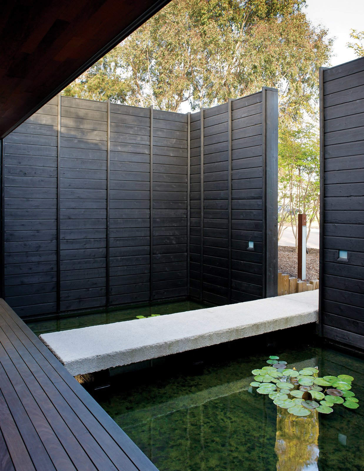 After entering through the front door, visitors pass over the large koi pond on a cast-concrete footbridge chiseled to look like stone. Tagged: Outdoor and Walkways.  Photo 3 of 7 in Sebastian Mariscal's Wood Architecture from An Atypical Modern Home in Southern California