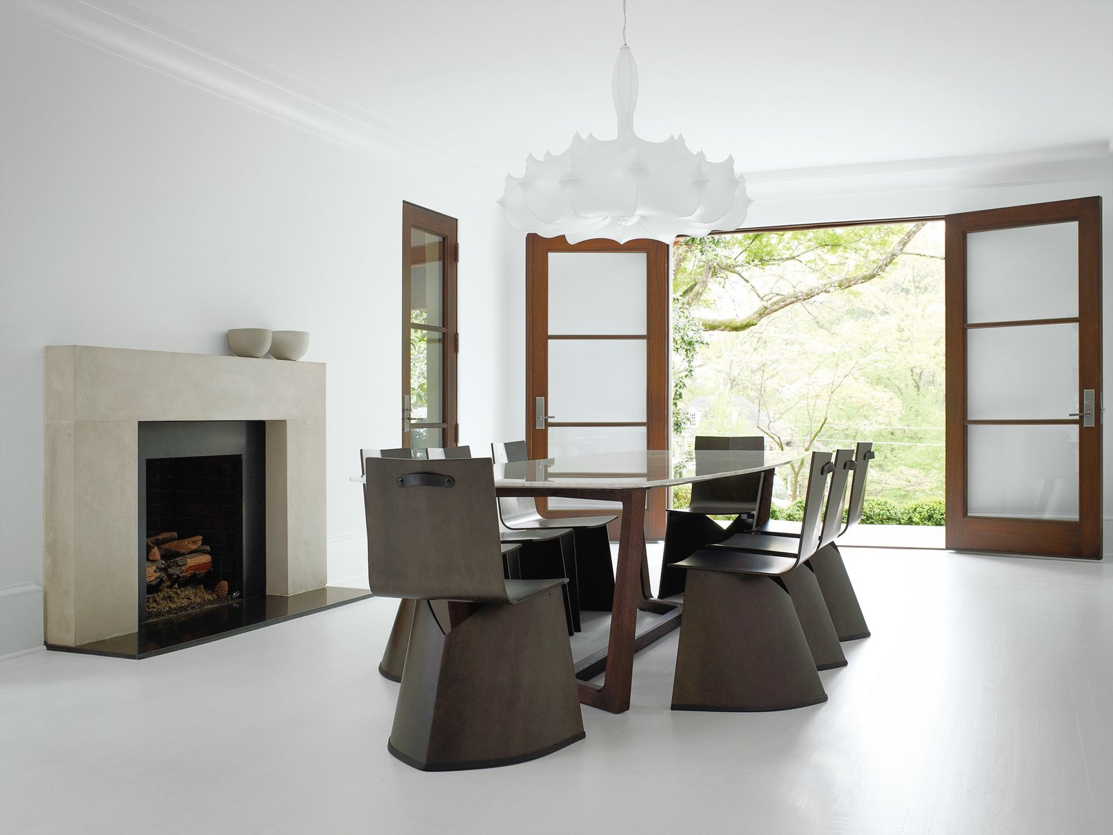 """Dining Room, Chair, Table, and Standard Layout Fireplace Konstantin Grcic's Venus chairs for ClassiCon surround a table by Poliform in the formal dining room. Hill selected the Flos chandelier designed by Marcel Wanders for its """"Old World reverence."""" The sleek fireplace mantel was designed by Hill and cobbled together onsite from three solid slabs of limestone.  Photo 5 of 9 in A Designer Brings Her Bold Brand of Texas Modern to this Atlanta Family Home from Barbara Hill on Designing Creative and Comfortable Rooms"""