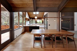 A renovated 1970s house in Washington features a string of dangling lights above the dining table. The table previously had an awkward placement around a column. For a more efficient solution, the architects simply embedded the table in the column, using carefully selected wooden supports that would match existing tones.