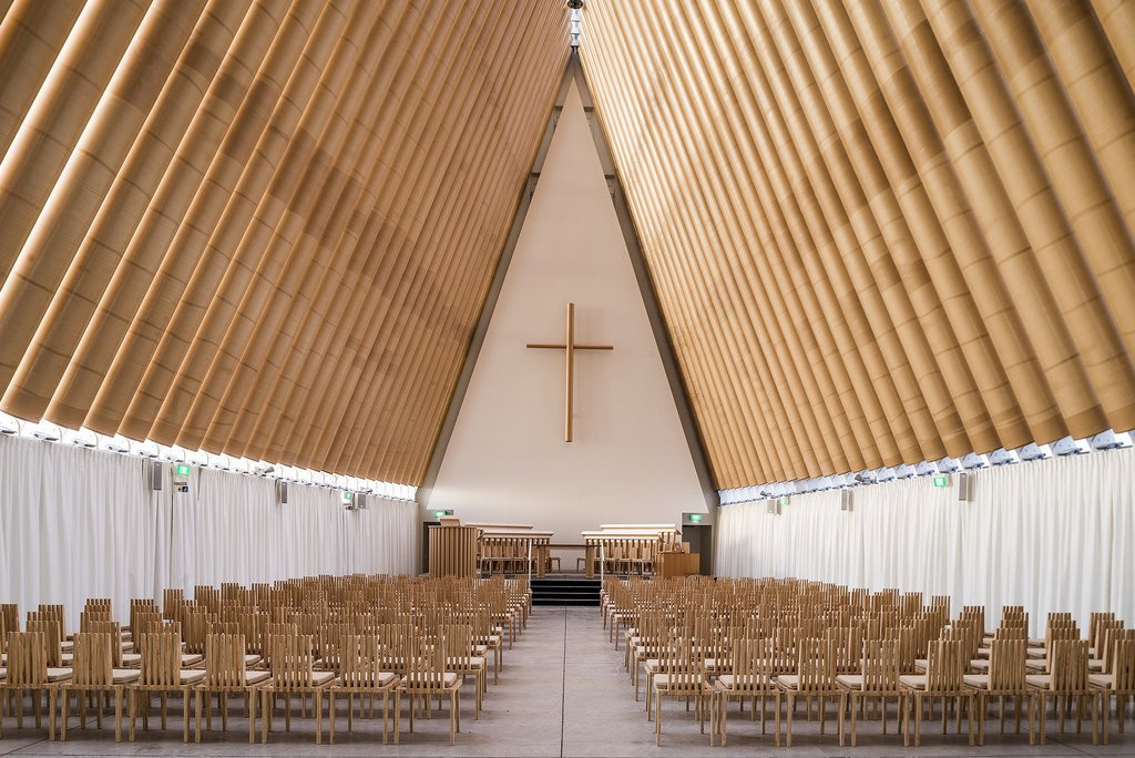 """Cardboard Cathedral (Christchurch, New Zealand: 2013)  After a massive earthquake destroyed this New Zealand town's landmark 19th-century cathedral in 2011, Ban crafted an A-frame out of cardboard tubing and shipping containers, a landmark example of his """"emergency architecture."""" In another nod to resiliency and symbolic rebirth, the stained glass triangle at the front of the church incorporates imagery from the former cathedral's famous rose window.  Photo 1 of 11 in 11 Buildings by Shigeru Ban"""