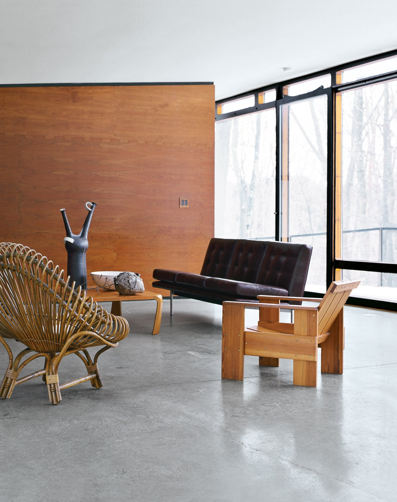 Living Room, Sofa, Chair, and Concrete Floor Architect William Massie built a hybrid prefab home for vintage retailer Greg Wooten, who handled the interiors. In the living room is a 1950s Franco Albini rattan chair, a Crate chair designed by Gerrit Rietveld in 1934, and a 1970s sofa by Edward Axel Roffman. The tall ceramic piece is by Bruno Gambone.  Photo 3 of 12 in A Hybrid Prefab Home in Upstate New York