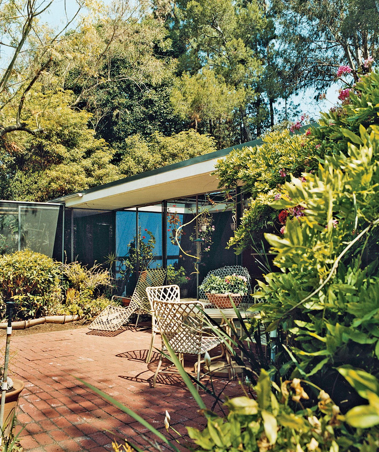 """At Shulman's insistence, Soriano created a screened area that protects the gardenside elevation of the house from, says the photographer, """"excessive wind and glaring light. In hot weather, when I have the sliding glass doors open, I close the screens on the sides—otherwise it's all open to the coyotes and raccoons."""" In keeping with the off-the-shelf ethic of the Case Study era, Soriano used simple, durable materials that, after 57 years, remain intact.  Photo 3 of 4 in True Hollywood Story"""