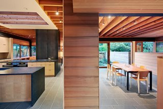Two long, narrow structures intersect in an open kitchen marked by a contrasting maple veneer, creating distinct programmatic areas that look out toward a lush, tree-lined landscape. Two operable skylights positioned over the kitchen release warm air while drawing in the cool.