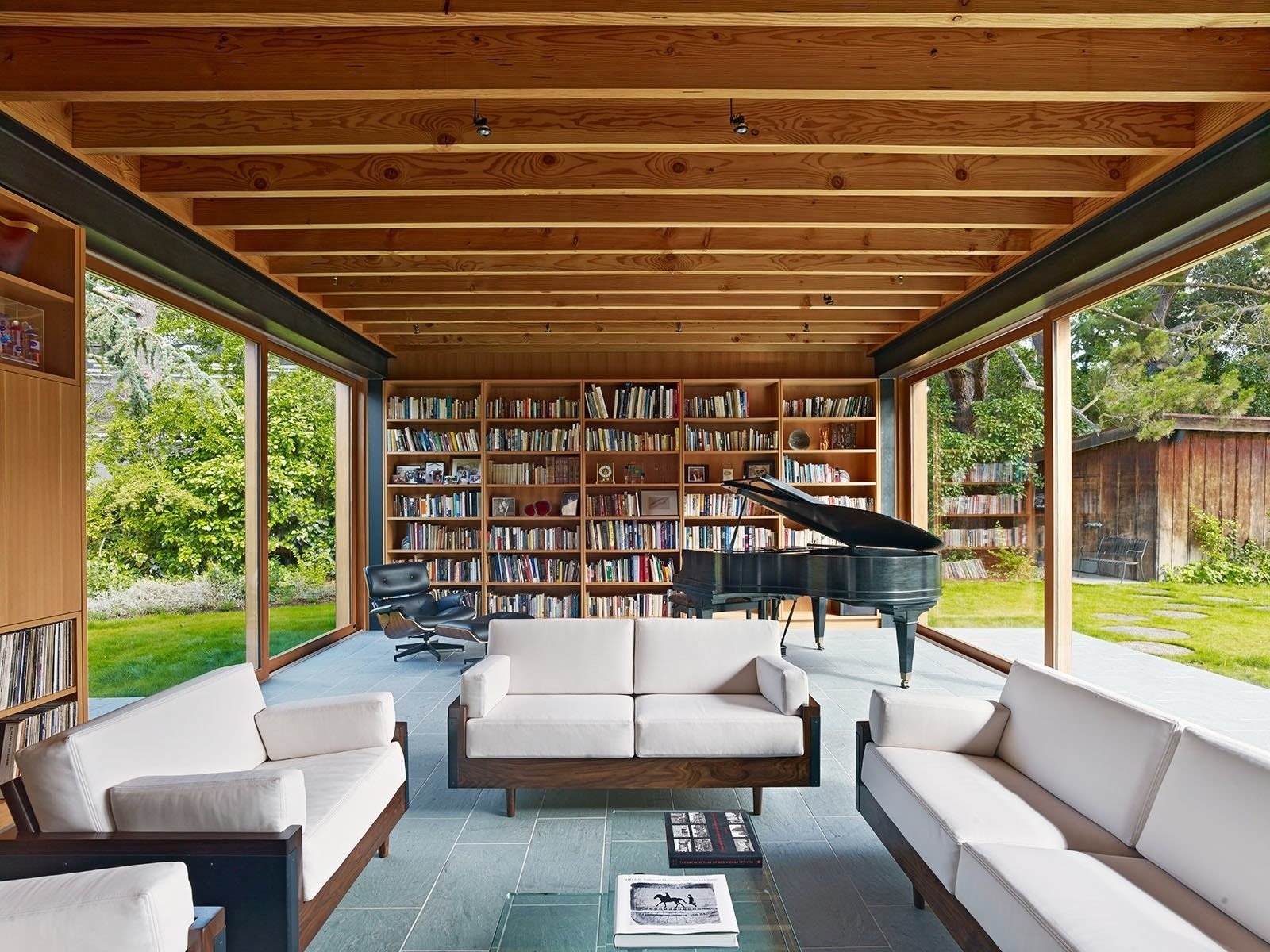 Living Room, Chair, Sofa, Slate Floor, Coffee Tables, and Bookcase Large sliding glass doors suspend the living room within the landscape for family gatherings or larger events.  Photo 3 of 8 in A Sustainable Home in Silicon Valley