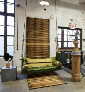 A unique custom porch swing hangs from the ceiling of the showroom.