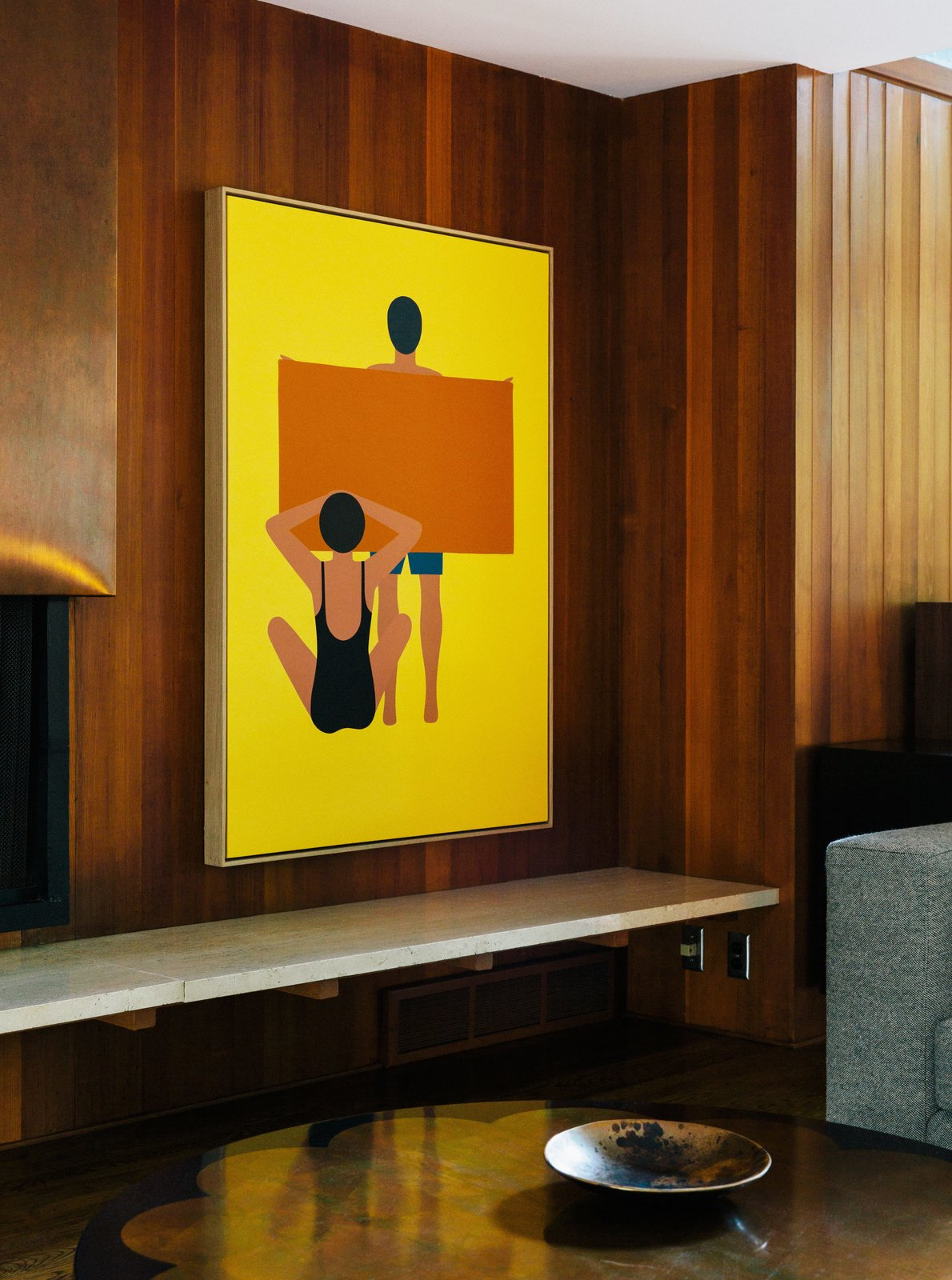 """In the living room, the painting is by Geoff McFetridge and the wood paneling is original to the house. """"Jewel-y color and simple shapes—they feel right in this house,"""" says interior designer Jessica Helgerson. Tagged: Living Room and Sofa.  Photo 4 of 11 in Wood Paneling Loses its Dated Reputation with This Renovation of a 1959 Portland Gem"""