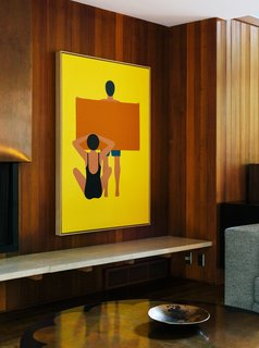 "In the living room, the painting is by Geoff McFetridge and the wood paneling is original to the house. ""Jewel-y color and simple shapes—they feel right in this house,"" says interior designer Jessica Helgerson."
