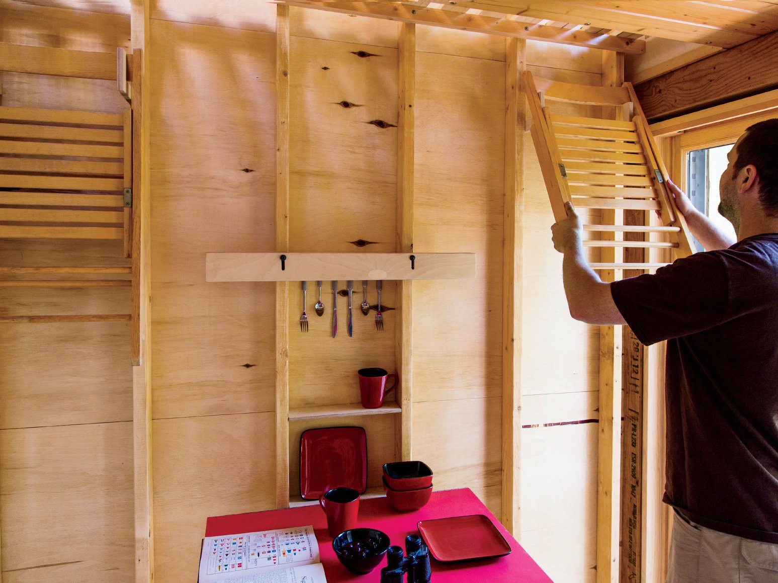 Daniel hangs a folding chair, Shaker style, on the wall adjacent to the entrance. The room gains extra light through slivers of space between the slats of the floor above. Structural two-by-fours and framing were left raw.  Photo 7 of 10 in Camping with Dad Just Got Cooler