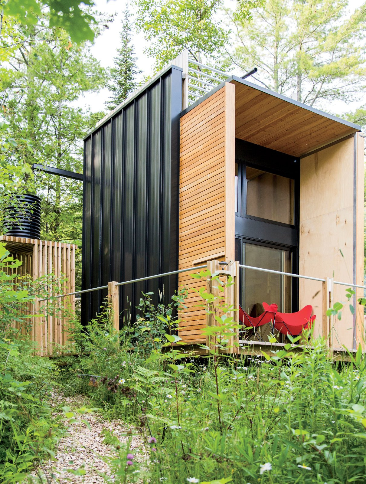 Exterior, Cabin Building Type, and Wood Siding Material A rainwater catchment system feeds a cistern and outdoor shower. The Butterfly chairs are from Hayneedle.  Photo 8 of 10 in Camping with Dad Just Got Cooler