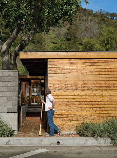 Flanking the concrete wall is a carport and an entrance leading past a small, cedar-clad ancillary building for art projects and laundry.  Photo 7 of 12 in Compound Addition