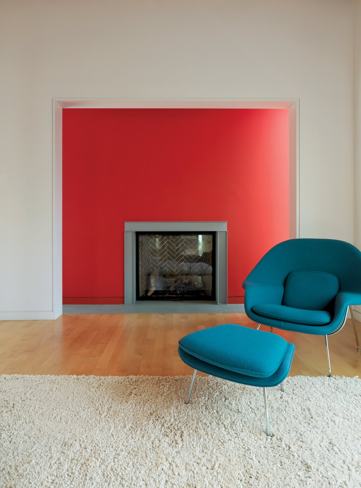 Living Room, Standard Layout Fireplace, Light Hardwood Floor, Rug Floor, and Chair In the living room, Fashandi enjoys lounging in the Saarinen Womb chair by Knoll near the fireplace. The red wall is flanked by thin windows, causing it to glow in the sunlight.  Photo 9 of 10 in Design Classic: Eero Saarinen's Womb Chair from Family Matters