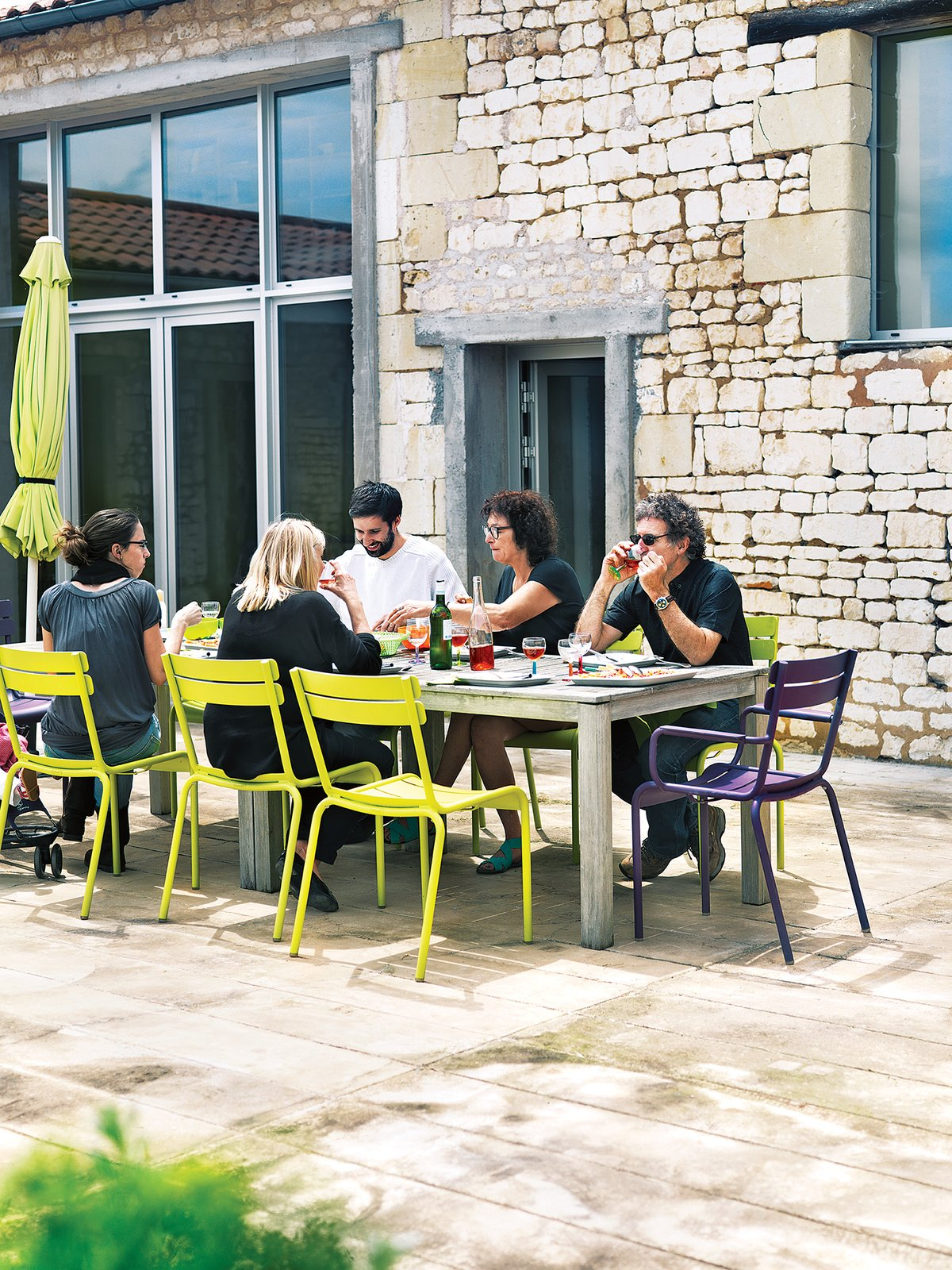 Outdoor Monory's friends, the Leclercs, join her for an alfresco meal on the patio. They're seated at a custom-made table on Fermob's Luxembourg chairs.  Photo 7 of 12 in Matali Crasset Renovates Monory Farmhouse