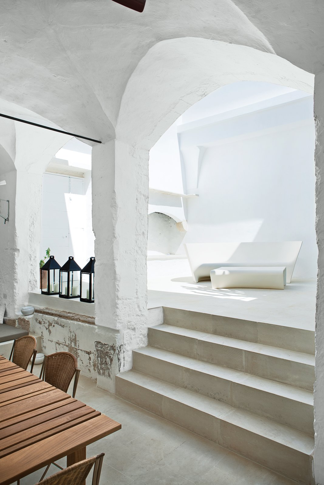 The indoor-outdoor Grand Plié sofa and Piaffé table, which the couple designed for Driade, perfectly suit the whitewashed courtyard, with curving silhouettes that echo the surrounding stonework. Serafini and Palomba purchased the metal lanterns at a local market.  Photo 4 of 8 in Modern Meets Ancient in a Renovated Italian Vacation Home