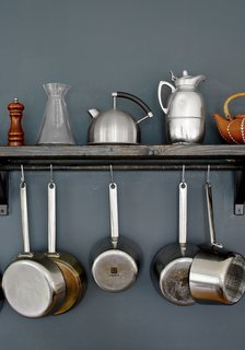 Small kettles and metal pots rest and hang on a wooden shelf in the kitchen.