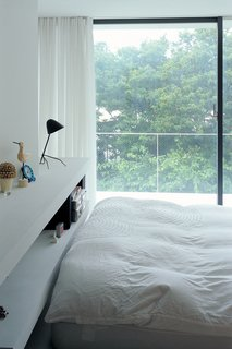 The bedroom has a view of the cherry trees.