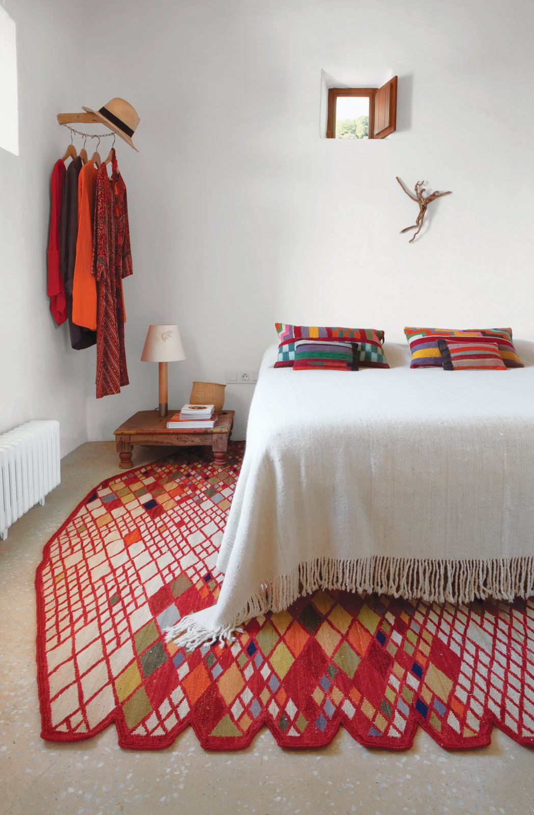 Bedroom, Bed, Night Stands, Table Lighting, and Rug Floor An earlier version of the Losanges rug, part of Marquina's 2011 collection, anchors the master bedroom of Nani Marquina's Ibiza home. Photo by Albert Font.  Photo 5 of 9 in When to Save Versus Splurge in Your Bedroom Revamp