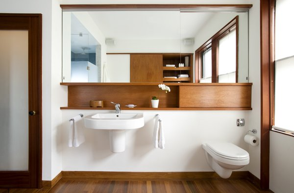 """""""Whenever you're making a minimal bathroom, you always have issues with storage,"""" Klug says. The wall-hung Duravitsink leaves no place """"to put all your junk,"""" so Klug and Butz added small shelf above. The space to the right, which appears as an extension of the shelf is actually a panel that hides access to the water tank of the wall-hung toilet, also by Duravit.Photo by   Eric Roth  Photo 3 of 4 in Loo & Improved"""