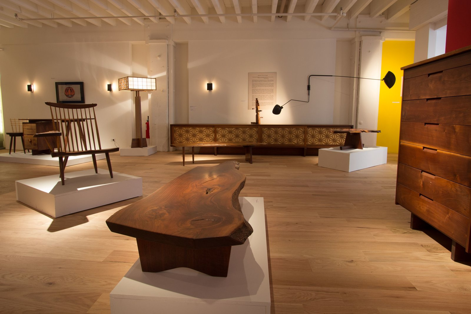 The exhibit includes the Shoki Collection (back left), the ASA-NO-HA Lamp (back wall), and an array of Nakashima originals.  Photo 1 of 4 in Exploring the process of George Nakashima Woodworker