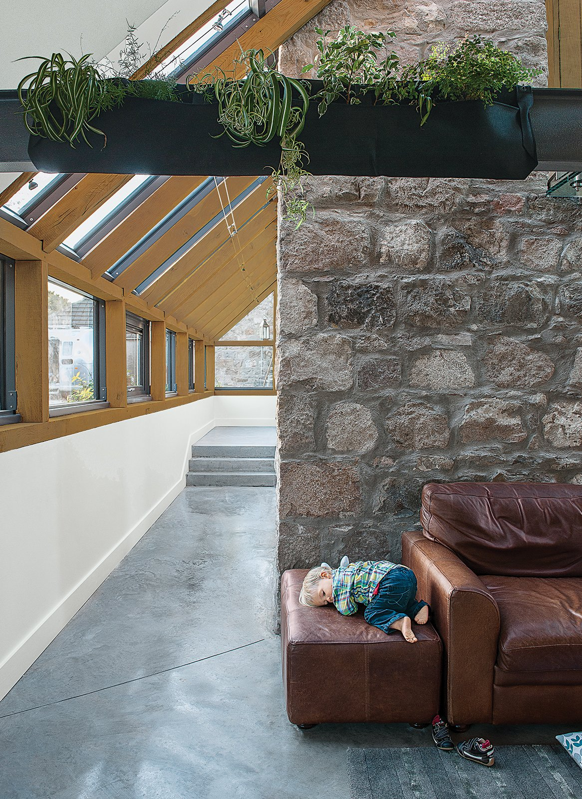 Living Room and Sofa A Woolly Pocket planter hangs on the steel beam above a polished-concrete floor warmed by radiant heat.  Photo 7 of 11 in This Farmhouse is a Cor-Ten Steel-Clad Dream