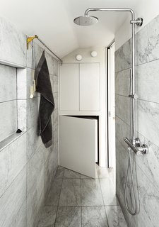 In a London apartment that measures less than 400 square feet, a small bathroom didn't have to mean that the space would be short on design or elegance. By using a textured-marble tile, Ullmayer Sylvester Architects and Rogeroger Design Solutions elevated the narrow bathroom and took advantage of built-in storage to create a sophisticated and effectively designed room.