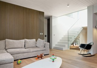 By straightening angles, installing windows, and adding vertical accents, architect Aaron Ritenour brought light and order to an irregularly-shaped apartment in the heart of Athens, Greece. Toys share space in the living room with an ETR coffee table and Molded Plastic Rocker chair, both by Charles and Ray Eames for Vitra. Behind the couch, 300 vertical oak strips add a decorative element.