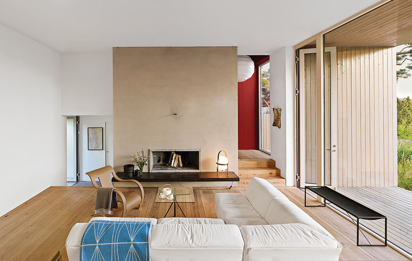 """In the living room, a sofa by Vico Magistretti is next to a plywood armchair by Gerald Summers. The coffee table is by Enzo Mari; the Cesta lantern is by Miguel Milá for Santa & Cole. """"It's too expected for us to put Hans Wegner here,"""" Duncanson explains. Tagged: Living Room, Chair, Medium Hardwood Floor, Sofa, Coffee Tables, and Wood Burning Fireplace.  Photo 2 of 8 in A Pine Box Vacation Home in Sweden"""