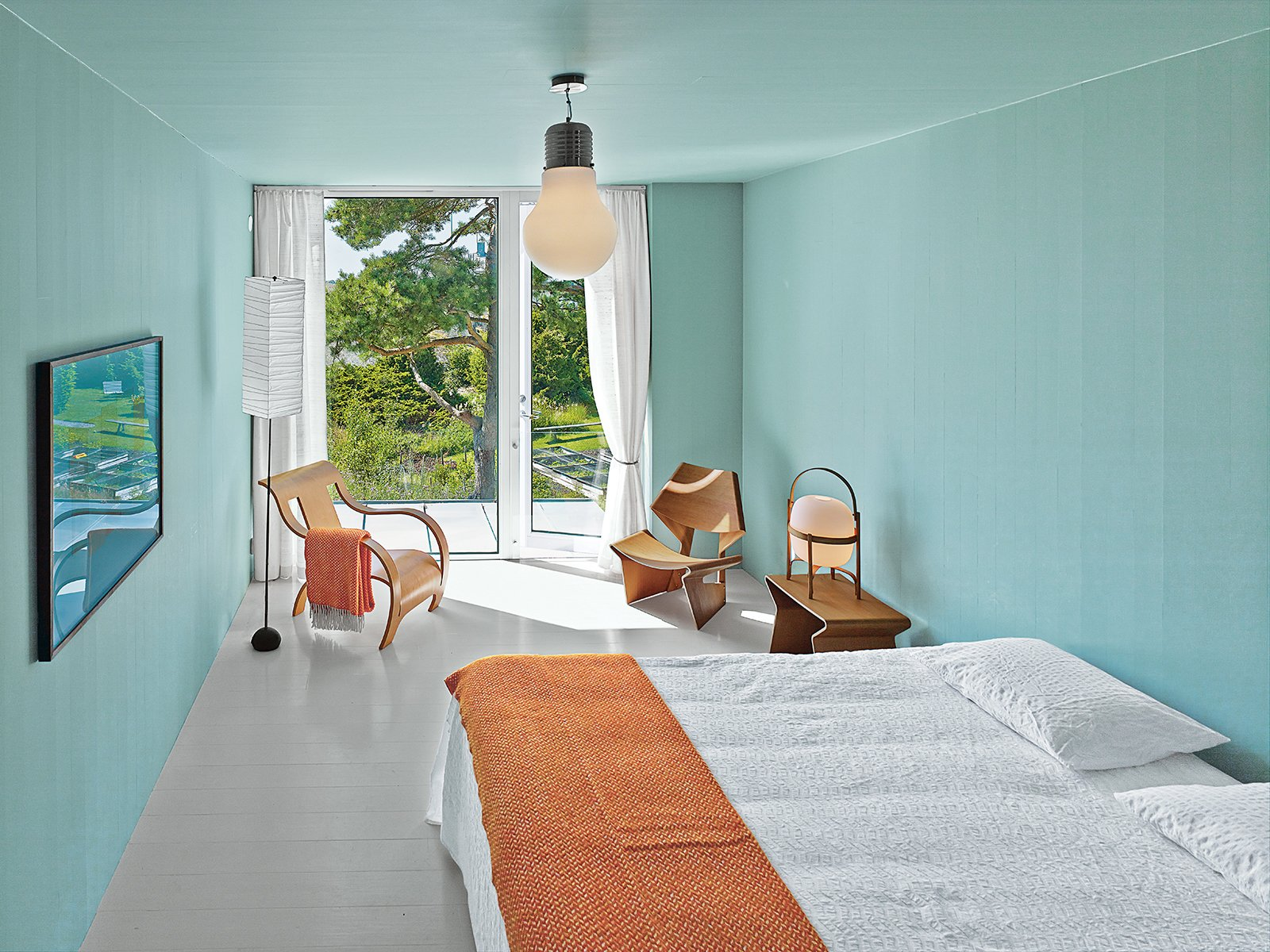 Bedroom, Night Stands, Chair, Bed, Lamps, Ceiling Lighting, and Painted Wood Floor The master bedroom, which is painted a soothing green-gray, features a chair and nesting tables in Oregon pine designed by Grete Jalk in the 1960s, and a standing lamp by Isamu Noguchi. The armchair is by Gerald Summers. The couple found the overhead fixture at an auction.  Photo 5 of 8 in A Pine Box Vacation Home in Sweden