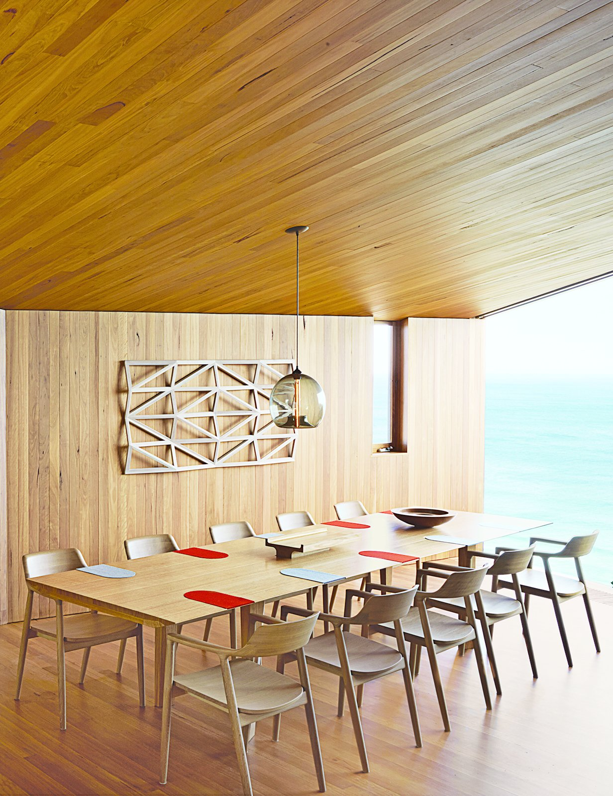 Dining Room, Chair, Pendant Lighting, Table, and Medium Hardwood Floor Wardle's firm also designed the dining table, where up to ten guests can gaze out at the Southern Ocean. The solid-oak Hiroshima chairs are designed by Maruni.  Photo 24 of 41 in 50 Dashing Dining Rooms from A Eucalyptus-Lined Oceanfront Home in Australia