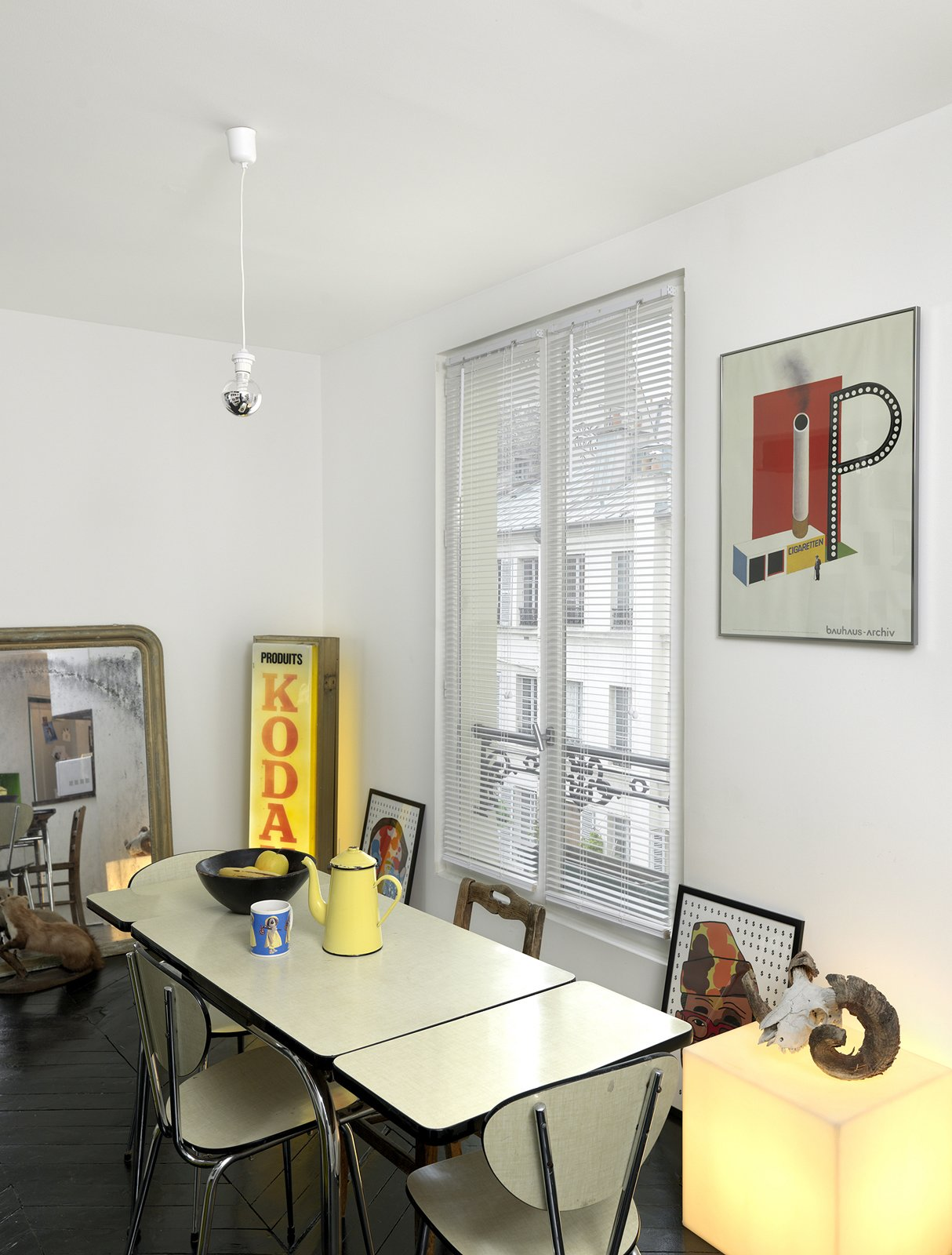 A simple poster with bold colors adds to the industrial character of this Paris abode. Photo by Céline Clanet. Tagged: Dining Room, Table, and Chair.  Photo 9 of 11 in 10 Dreamy Parisian Homes from Shelf Life
